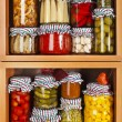 Many glass bottles with preserved food in wooden cabinet Isolated on white background — Stock Photo #36635653