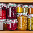 Many glass bottles with preserved set food in wooden cabinet — Stock Photo #36635885