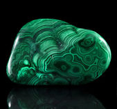 Polished malachite stone close up with reflection on black surface background — Stock Photo