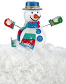 Funny snowman in a striped scarf, mittens with blue hat, sitting on a snowdrift isolated on white background — Stock Photo