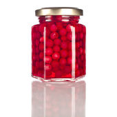 Cowberry in glass jar close up isolated on a white background — Stock Photo
