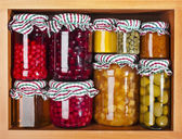 Many glass bottles with preserved set food in wooden cabinet — Stock Photo