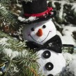 Happy Christmas snowman sitting in a snowy winter conifer fir tree — Stock Photo #38075453