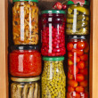 Many glass bottles with preserved food in wooden cabinet — Stock Photo #38075585