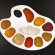Collection of various spices on a art palette on black wooden surface table, top view — Stock Photo #38076035