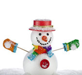 Funny snowman in a striped scarf , mittens with red hat , sitting on a snowdrift isolated on white background — Stock Photo