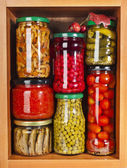 Many glass bottles with preserved food in wooden cabinet — Stock Photo