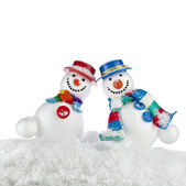 Cheerful dancing snowmans in a striped scarfs, mittens and cylinder hat isolated on white background — Stock Photo