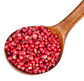 Pink peppercorn in a wooden spoon, on white background — Stok fotoğraf