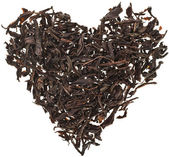 Black Ceylonese tea leaf in shape heart isolated on white background — Stock Photo