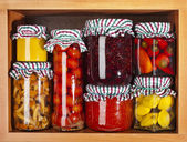Many glass bottles stack with preserved food in wooden cabinet — Stock Photo