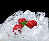 Frozen strawberries on ice cubes surface background — Stock Photo