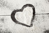Heart of flour on black wooden surface — Stock fotografie