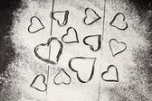 Wheat flour with hearts shape — Stock Photo