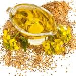 Flower Oil in gravy boat and mustard flower — Stock Photo #42051683