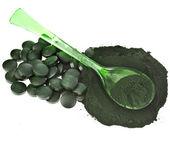 Spirulina algae powder and tablets in spoon — Stock Photo