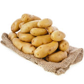 Raw potatoes heap with sack — Stock Photo