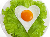 Fried egg in shape of heart on a plate — Stockfoto