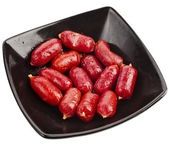 Sausages on black plate bowl — Stock Photo
