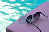 Sunglasses by the swimming pool. — Stock Photo