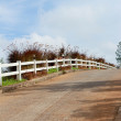 Foto de Stock  : White fence with road