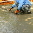 Pouring concrete mix for road construction workers. — ストック写真