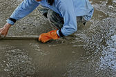 Pouring concrete mix for road construction workers. — Stockfoto