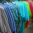 Shop shirts colorful fabric hanging on a rack. — Stock Photo