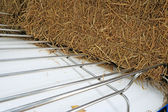 Part blue vintage car with a pile of straw. — Stock Photo
