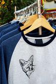 Camisas de loja pendurado num mercado de cremalheira — Fotografia Stock