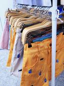Shop pants hanging on a rack market. — Stock Photo