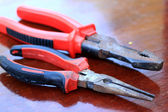 Pliers red handle tool on the wood — Stock Photo
