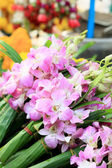 Pink orchids tied together at the market. — Stock Photo