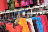 Shop shorts colorful fabric hanging on a rack. — Stock Photo