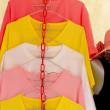 Shop shirts colorful fabric hanging on a rack. — Stock Photo #44980647