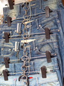 Shop vintage jeans hanging on a rack. — Stock Photo