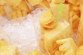 Close-up fresh pineapple place stacked in ice. — Stock Photo