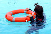 Girl swimming in the pool wearing life ring  — Foto Stock