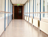 Long empty corridor with an emergency exit sign — Foto Stock