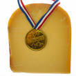 A piece of cheese with a winner's medal on a white background — Stock Photo