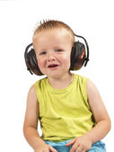 Toddler sitting with headphones on his head on a white background — Stock Photo
