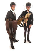Two handsome young men with horses outfit and a rocking horse — Stock Photo