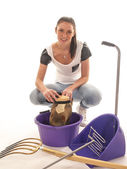 Beautiful girl with horses cleaning equipment — Stock Photo