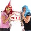 Two cheerful ladies in party mood with a billboard — Stock Photo