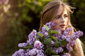 Beautiful blonde girl with lilac flowers in the sunset light, se — Стоковое фото