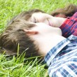 Young couple laying on grass — ストック写真