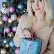 Christmas blonde woman with a present — Stock Photo