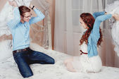 Young couple doing pillow fight — Stock Photo