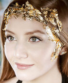 Beautiful caucasian woman with golden makeup — Stock Photo