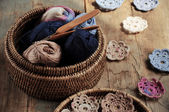 Box of yarn and crocheted flowers — Stock Photo